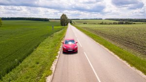red car on road between green grass field during daytime